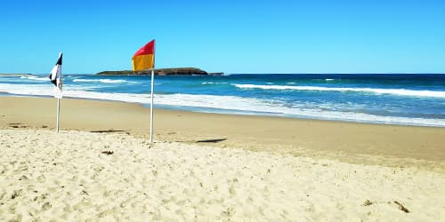 Warilla beach with flags and Windang Island